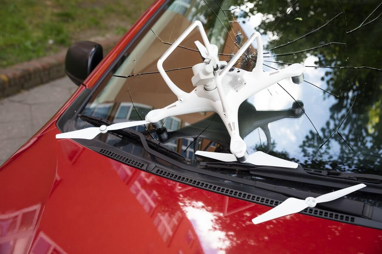 Closeup of damaged white drone on broken car windshield